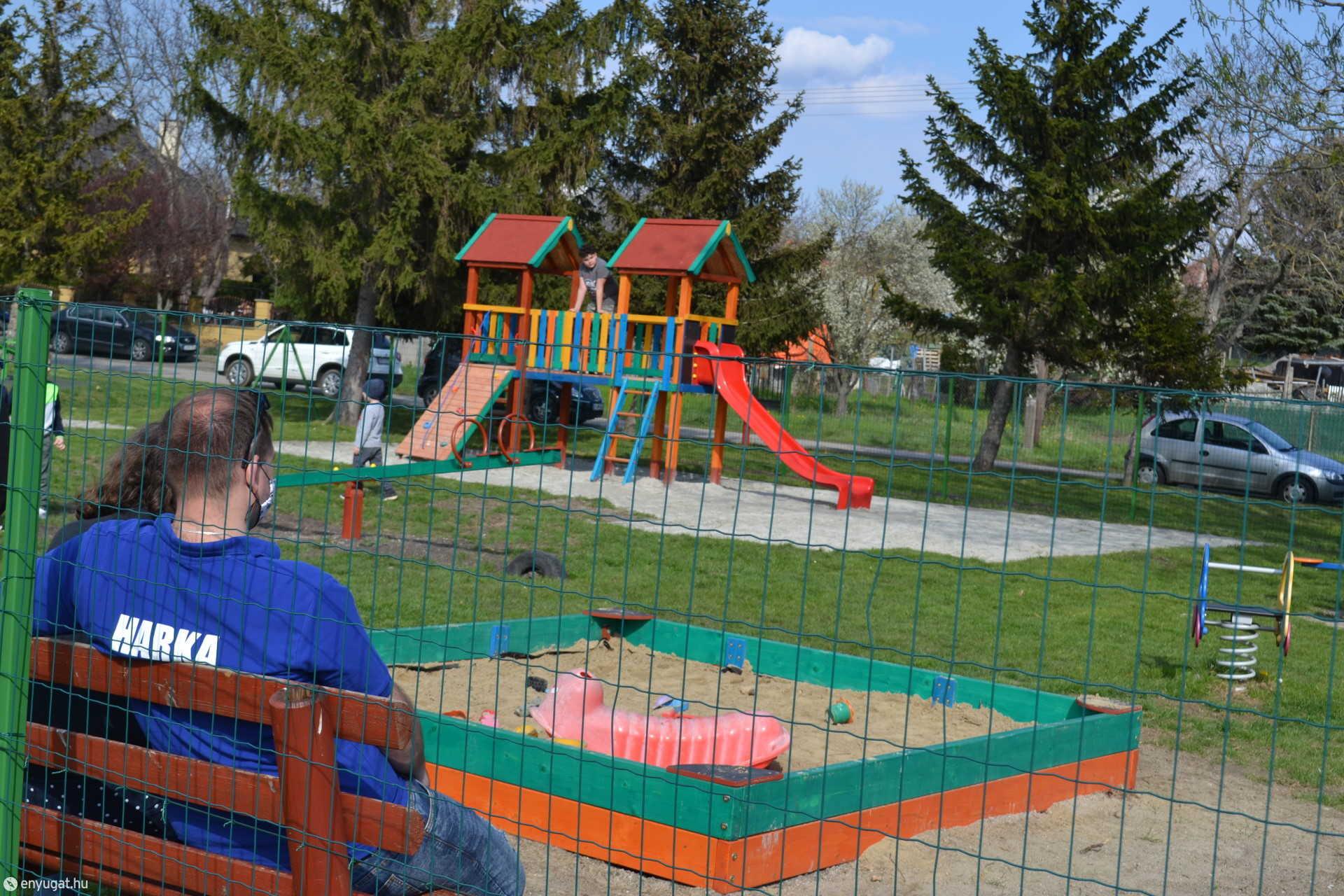 A játékszerek egy tágas, füves területen biztonságos játékot biztosítanak a harkai kicsiknek.